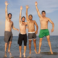 Four friends jumping men on a beach Stock Photos
