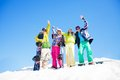 Four friends with snowboards standing in snow happy and waiting hands Stock Photography