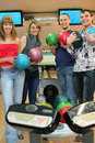 Four friends stand near tenpin bowling with balls Royalty Free Stock Photo