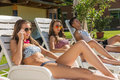 Four friends sunbathe on the sun loungers on the beach Royalty Free Stock Images