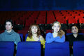 Four friends watch movie in cinema theater young focus on girls Royalty Free Stock Photos