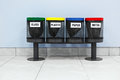 Four garbage bins on wall background Royalty Free Stock Photo
