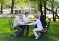 Four generations of men sitting at a wooden table in a park, laughing and talking Royalty Free Stock Photo
