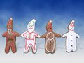 Four gingerbread cookie figures two snowman and two santa clause shape with color icing shot on blue background Stock Photography