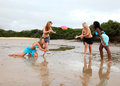 Four girls playing beach rugby of different races are on the they are having and laughing Royalty Free Stock Photography