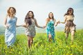 Four girls running in the fields concept about spring time happiness nature women and people Royalty Free Stock Photography
