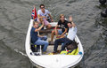 Four guys in a sloop amsterdam holland august wave to onlookers during the sail event amsterdam holland on august Stock Photo