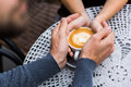 Four hands wrapped around a cup of coffee Royalty Free Stock Photo