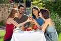 Four happy attractive young friends enjoying a healthy meal sitting at a table together in the garden eating fruit Royalty Free Stock Photos