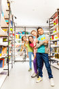 Four happy kids standing in a row with books library and boy front holding exercise book Royalty Free Stock Images
