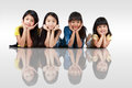 Four happy little asian girls laying on the floor isolated over white with shadows Royalty Free Stock Photos