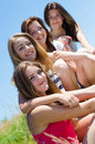 Four happy smiling young women sitting together against blue sky teen girls on summer outdoors background Royalty Free Stock Photo