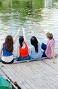 Four happy teen friends sitting on pier of river or lake and pointing copyspace over them summer outdoors background Royalty Free Stock Photos
