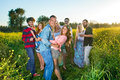 Four happy young couples having a party in the countryside dancing and laughing together in colorful yellow rapeseed field Royalty Free Stock Images