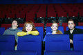 Four happy young people rest in movie theater focus on left girl Royalty Free Stock Photo