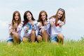 Four happy young women friends showing thumbs up in green grass over blue sky smiling teenage Royalty Free Stock Image