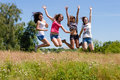 Four happy young women girls friends jumping high against blue sky girl on summer green outdoors background Stock Image