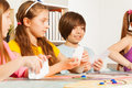 Four kids playing cards for a pastime friends blanked Stock Images