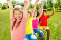 Four kids sitting in row with hands up Royalty Free Stock Photo