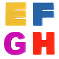 Four letters written in multicolored plastic kids letters Stock Photos