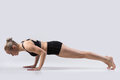 Four limbed staff pose sporty beautiful young woman practicing yoga doing chaturanga dandasana for abdominal muscles shoulders and Royalty Free Stock Photo