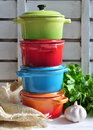 Four little colorful cooking pots and linen texture