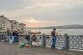 Four men fishing on galata bridge over bosphorus strait on daybr istanbul turkey jun were facing when sunlight just broke clouds Stock Images
