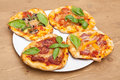 Four mini pizzas different kinds of small pizza on a white plate on wooden table Stock Images