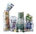 Four money jars overflow with euro russian american and chinese bank notes and coins against white background Royalty Free Stock Photos