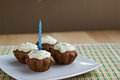 Four muffins with one candle Stock Images