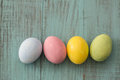 Four pastel colored Easter eggs on blue wood background