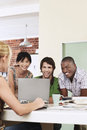 Four people having meeting around laptop laughing Stock Photos