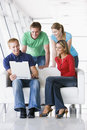 Four people in lobby looking at laptop smiling Royalty Free Stock Photo