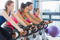 Four people working out at spinning class Royalty Free Stock Photo