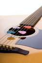 Four picks in guitar strings vertical photo of front side of acoustic with bridge and fretboard colorful are placed Royalty Free Stock Photo