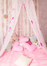 Four-poster bed with pink pillows Royalty Free Stock Photo