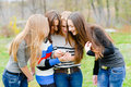Four pretty young women in spring or autumn outdoors using mobile phone Royalty Free Stock Images