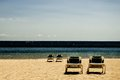 Four reclining chairs on a beach (contrast) Royalty Free Stock Photo