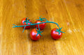 Four red cherry tomatoes on a branch on a wooden Royalty Free Stock Photo