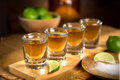 Four shot glasses with tequila bottle and bowl of limes with salt at a bar golden shots lime served mexican restaurant table to Royalty Free Stock Photography