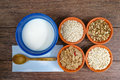 Four small bowls with different cereals and bowl with milk, healthy food Royalty Free Stock Photo