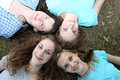 Four smiling attractive teenage girls lying on their backs on green grass with their heads together looking up at the camera Stock Image