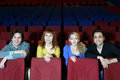 Four smiling friends sit on seats in cinema theater young and see movie Royalty Free Stock Photography