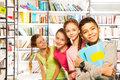 Four smiling kids standing in a row with books library and boy front holding exercise book Royalty Free Stock Image