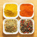 Four spices red ground pepper black pepper curry powder and herb in bowls Stock Image