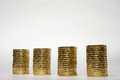 Four stacks of coins on light background Royalty Free Stock Photo
