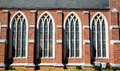 Four stained glass windows in a brick church Stock Photo