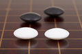 Four stones during go game playing on goban close up Royalty Free Stock Image
