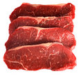 Four striploin steaks on white Stock Photography