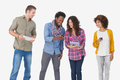 Four stylish friends looking at tablet and holding phones on white background Royalty Free Stock Images